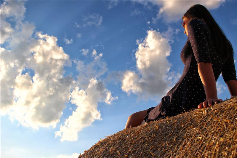 Woman sitting on haystack and watching the sunset