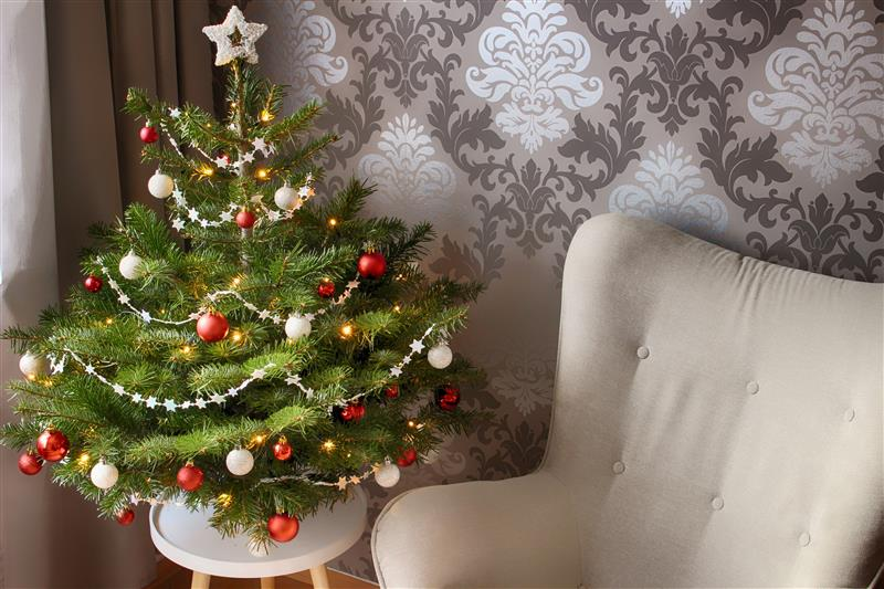 Beautiful christmas tree nearby armchair
