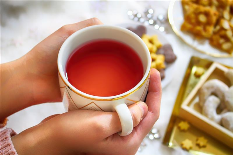 Holding a cup of tea and christmas sweets