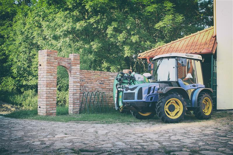 Tractor with sprayer near the brick wall