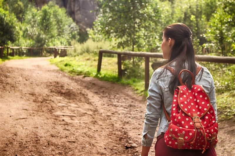 Woman on dirt road with a red backpack