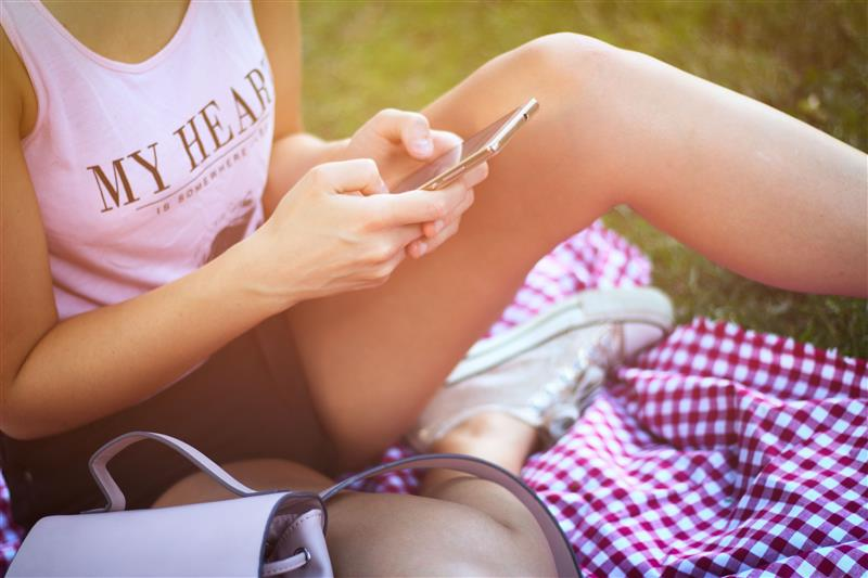Woman sitting on picnic blanket and typing message on phone