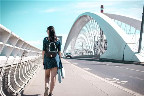 Girl with backpack on the bridge