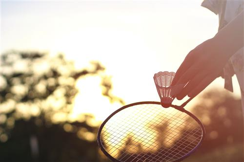 Holding badminton racket at sunset